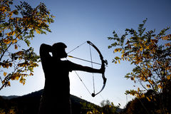 Archer drawing his compound bow silhouette Stock Photos