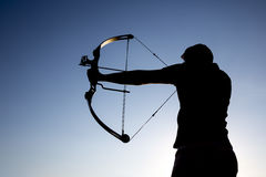 Archer drawing his compound bow silhouette Royalty Free Stock Image