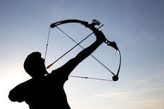 Archer drawing his compound bow silhouette Royalty Free Stock Photography