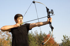 Archer drawing his compound bow trees Stock Image