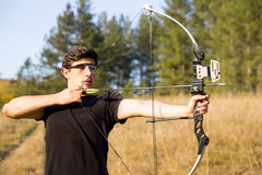 Archer drawing his compound bow trees Stock Photography