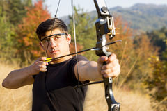 Archer drawing his compound bow trees Royalty Free Stock Image
