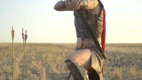 Archer en la armadura de cuero se coloca en rodilla en el medio del campo y tiene como objetivo la cámara, cámara lenta metrajes