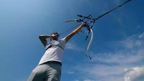 Archer está tirando de la cuerda de arco y se está preparando para tirar Tiroteo con un arco y las flechas almacen de video
