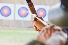 Archer holds his bow aiming at a target Stock Photos
