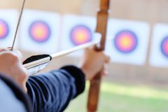 Archer holds his bow aiming at a target Royalty Free Stock Photos