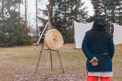 Archer looks at straw target with arrows in the center Royalty Free Stock Image