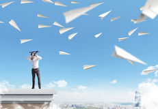 Archer paper planes. Archer standing on pedestal aiming at paper planes on sky background royalty free stock photos