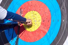 Archer pulls arrows from target royalty free stock photography
