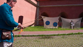 Archer Shoots at the Target. Archer in the medieval clothes archery at targets on the background of the fortress wall stock video