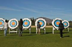 Archer som samlar pilar från målen i fältet Fotografering för Bildbyråer