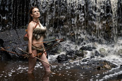 Archer stands in the water with the bow and arrow Stock Photo