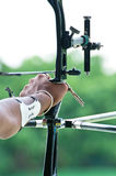 An archer takes aim at a target during competiton. An archer with bow takes aim at a target during competition stock images