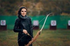 Archer Woman con el arco y la flecha en el entrenamiento de la blanco Foto de archivo