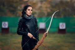 Archer Woman con el arco y la flecha en el entrenamiento de la blanco Imagenes de archivo