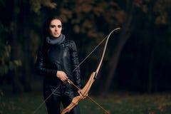 Archer Woman con el arco y la flecha en el entrenamiento de la blanco Foto de archivo libre de regalías