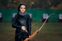 Archer Woman con el arco y la flecha en el entrenamiento de la blanco Imagen de archivo libre de regalías