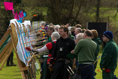 Archers lookings at arrows in row of targets Stock Image