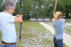 Archery athletes aiming at target in distance Royalty Free Stock Photos