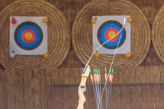 Archery bow, arrows and targets. Archery bow and some arrows in front of targets Royalty Free Stock Photo