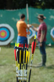 Archery lesson. Archery arrows in the foreground with an archer getting some tuition in the blurred background. Sports related or business articles about Stock Images
