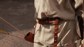 Man with brown belt with metal inserts, pulls arrows from special bag for bow