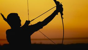 Archery silhouette, sun sets behind the archer. Young hunter.