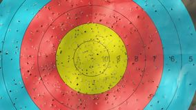 Archery target with arrow holes moving in on bullseye. Gold, red, blue and black competition target marked where arrows have penetrated, with dappled shadows stock video