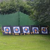 Archery targets outdoors with large green marquee. Five archery targets upright on the grass with a large green marquee close by. Some bunting is also in the Stock Images