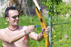 Archery. Young man holding back an arrow and aiming to shoot Royalty Free Stock Photo