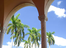 Through the Arches. View of palm trees through arches of Mediterranean building, with bright blue sky and white clouds in the background royalty free stock photos