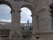 Arches of an amphitheater in Pula, the church bell tower in the background stock photography