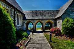 Arches in breezeway. Connecting stone buildings of a church on lake shore Stock Photos