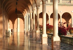 Arches and Columns of southern mansion. Long corridor of southern mansion, showing arches and columns, with large pots of red bougainvillea along tiled walkway stock photography