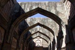 Arches at Hindola Mahal, Mandu. Attractive stone arches at roofless Hindola Mahal or Swinging Palace audience hall with sloping side walls at Mandu, Madhya Stock Image