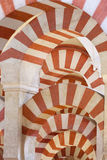 Arches in Moorish mosque. A compressed view of red-and-white arches in the Great Mosque of Cordoba Royalty Free Stock Photography