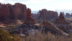 Arches National Park 05. With bushes in the foreground, the camera trucks from right to left as it overlooks a beautiful vista full of natural stone monuments in stock video footage