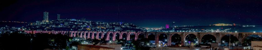 The Arches, Night Illuminated of The Aqueduct in Queretaro. Seventy four arches form the aqueduct in Queretaro Mexico. It`s an ancient structure and iconic stock photos