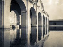 Arches over water. Arched structure spans waterway.  Arches are reflected in water.  Antigua, Guatemala Royalty Free Stock Photography