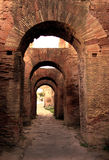 Arches on Palatine Hill, Rome. Ancient Roman arches made of red bricks flanking a road found on Palatine Hill in Rome Royalty Free Stock Photo