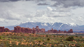 Arches panorama and snowcapped mountains in the background Stock Image