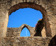 Arches of San Juan Mission in Texas. View of an old arch in San Juan Mission in Texas with modern jet trail in sky stock photography