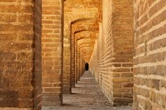 Arches of Siosepol on bridge in Isfahan. Arches of Siosepol - old brick bridge in Isfahan. Iranian women dressed in black at the end of the sidewalk Stock Photography