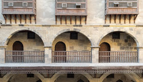 Arches with wooden balustrades, caravansary Wikala of Bazaraa, Cairo, Egypt. Front view of three arches with interleaved wooden balustrades at the arcade Stock Photography