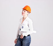 Archictures in Safety Helmet and Architectural Plans. Architectress in Orange Safety Helmet is Holding Architectural Plans  on White Background Royalty Free Stock Images