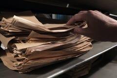 Archief van documenten op de plank Close-up van een mensen` s hand De man in de bibliotheek royalty-vrije stock foto's