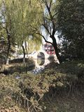 Arching Bridge of China. An arching bridge in China on far shore of a small pond that is surrounded by trees royalty free stock photography