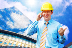 Architect. Young architect wearing a protective helmet standing on the building background Stock Photo