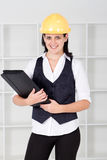 Architect. Portrait of a young female architect wearing a construction hat and holding a file Royalty Free Stock Photography