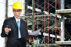 The Architect. An architect or construction engineer examine a construction plan while taking a phone call Stock Photo